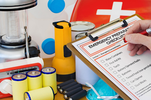 Emergency Prep check list and items hand with pen and clipboard