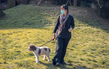 Photo of woman with face covering walking a dog